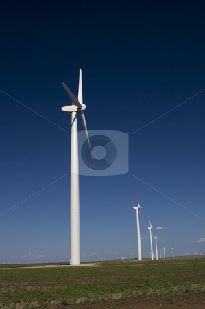A Line of White Wind Turbines stock photo, A line of wind turbines reaches to the horizon. by Charles Buegeler