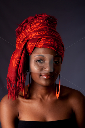 African woman with headwrap stock photo, Beautiful African-American woman wearing a traditional tribal red orange head scarf and orange earrings, isolated. by Paul Hakimata