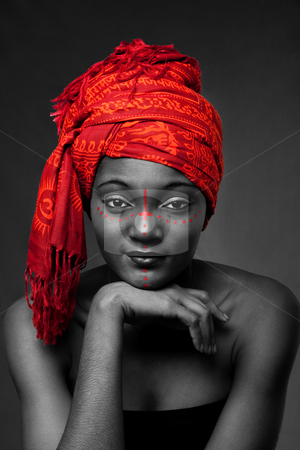 Tribal African woman with headwrap stock photo, Beautiful traditional African-American woman wearing a authentic tribal red orange head scarf and red dotted makeup, supporting her chin with hand, isolated. by Paul Hakimata