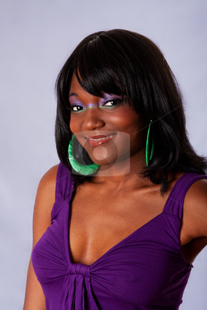Beautiful African woman smiling stock photo, Portrait of a young beautiful African-American woman dressed in purple and purple-green makeup with long straight black hair, smiling, isolated by Paul Hakimata
