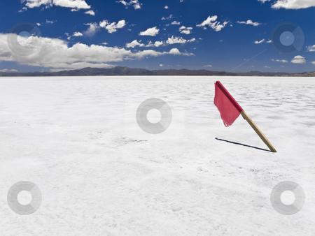 High noon stock photo, A red flag stuck in a huge salt field. by Ignacio Gonzalez Prado