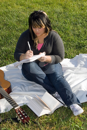 Musician Writing a Song stock photo, A young musician writing in her notebook while sitting in the grass on a nice day. by Todd Arena