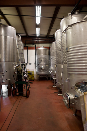 Wine Storage Tanks stock photo, Modern aluminum storage tanks where grape juice is aged into wine located in a vineyard cellar. by Todd Arena