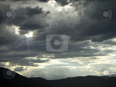 Stormy hope stock photo, A hole in a stormy cloud let a ray of light pass through. by Ignacio Gonzalez Prado