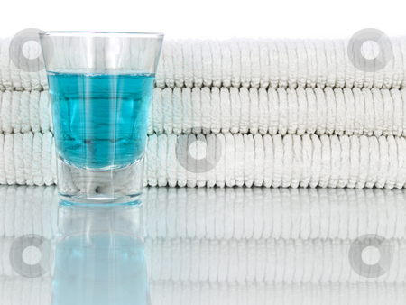 Mouthwash and towels stock photo, A glass full of mouthwash on a background of clean and white towels. by Ignacio Gonzalez Prado