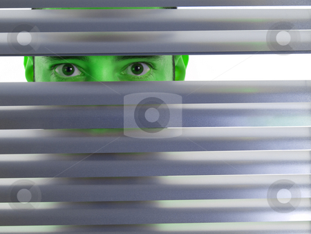 Green peeping Tom stock photo, A green man looks to the camera through the blinds. by Ignacio Gonzalez Prado