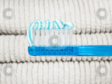 Toothpaste worm stock photo, A blue toothbrush full of toothpaste with white towels as background. by Ignacio Gonzalez Prado