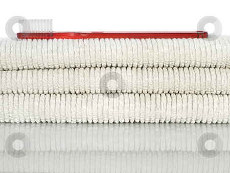 Red toothbrush and towels stock photo, A red toothbrush over a few white towels. by Ignacio Gonzalez Prado
