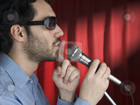 Pipe down stock photo, A young man with sunglasses hushing the audience on the mic. by Ignacio Gonzalez Prado