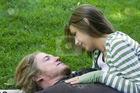 Young couple hugging in a park stock photo, Young Married couple laying down on the grass in a park by Mehmet Dilsiz