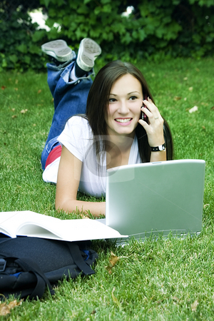 Cute teen girl laying down on the grass studying stock photo, Cute teen girl laying down on the grass studying with her laptop by Mehmet Dilsiz