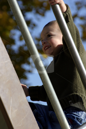 Kid Climbing Up the Slider stock photo, Kid Climbing Up the Slider with a Smile on His Face by Mehmet Dilsiz