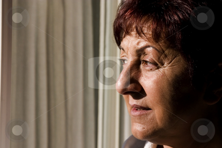 Woman looking out the window stock photo, Woman looking out the window towards the sun by Mehmet Dilsiz