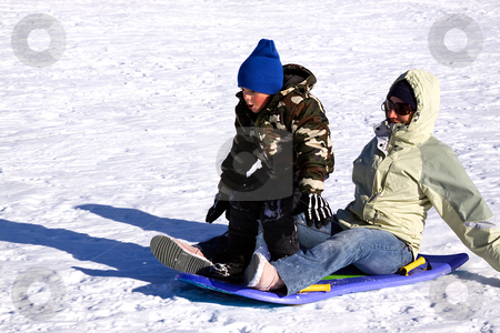 Mother and two Sons Sledding down the Hill stock photo, Mother and Son Sledding down the Hill While the Boy is Trying to Stand Up by Mehmet Dilsiz