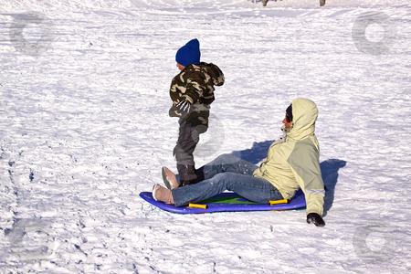 Mother and Son Sledding down the Hill stock photo, Mother and Son Sledding down the Hill while the Boy Trying to Stand Up by Mehmet Dilsiz