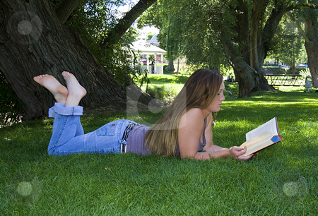 Beautiful Girl in the Park Reading a Book stock photo, Close up on a Beautiful Girl Laying Down in the Park Reading a Book by Mehmet Dilsiz