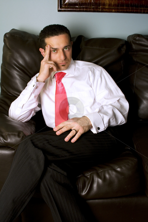 Businessman on the Couch stock photo, Close up on a Businessman Looking at the Camera by Mehmet Dilsiz