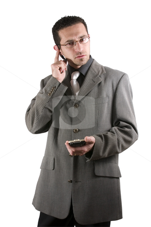 Businessman on the PDA phone with an ear piece stock photo, Businessman on the phone with PDA in hand and an earpiece by Mehmet Dilsiz