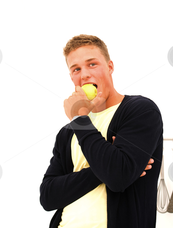 Handsome young man eating an apple  stock photo, Handsome caucasian young man eating an yellow apple with blue vest by Karin Claus