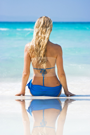 Blonde on the beach with reflection stock photo, Blonde girl on the beach and looks at the sea by Dmitry Rostovtsev