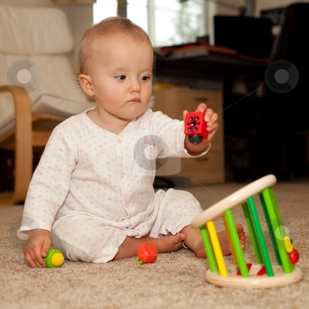 Playing on the floor stock photo, Cute Caucasian baby girl playing on a floor. by Mariusz Jurgielewicz