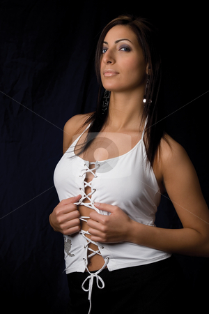 Pulling on clothes stock photo, Twenty something fashion model in sexy corporate style pulling the middle of her blouse looking at the camera by Yann Poirier