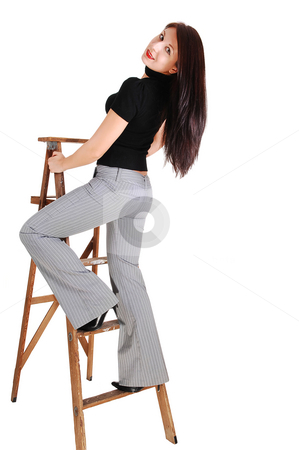 The body of a young woman. stock photo, An young woman standing on the step of a stepladder in a gray dress pants and black sweater, shooing her fantastic body. by Horst Petzold