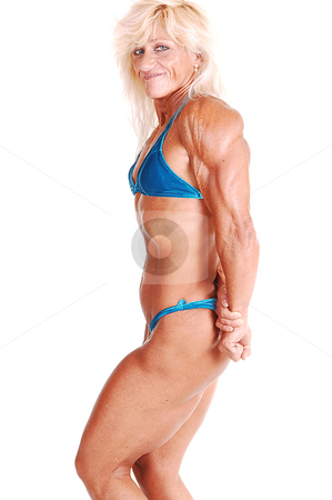 Bodybuilding woman. stock photo, A strong blond woman in an blue bikini, standing bare foot in the studio and shooing her muscular body and bicep, over white. by Horst Petzold