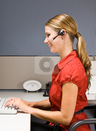 Businesswoman talking on headset at desk stock photo, Businesswoman talking on headset at desk by Jonathan Ross