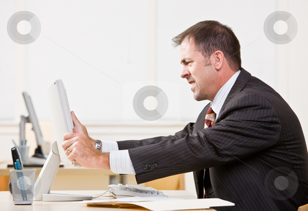 Businessman adjusting computer monitor stock photo, Businessman adjusting computer monitor by Jonathan Ross