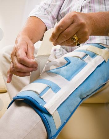 Senior woman adjusting knee brace stock photo, Senior woman adjusting knee brace by Jonathan Ross