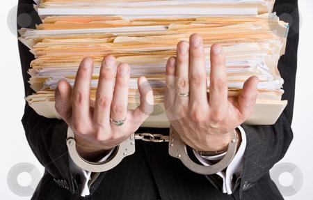 Businessman in handcuffs holding file folders stock photo, Businessman in handcuffs holding file folders by Jonathan Ross