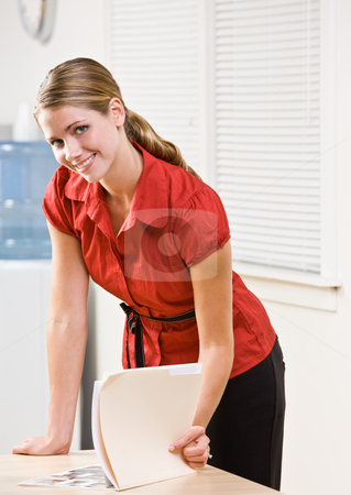 Businesswoman looking at file folder stock photo, Businesswoman looking at file folder by Jonathan Ross