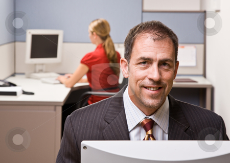 Businessman sitting at desk smiling stock photo, Businessman sitting at desk smiling by Jonathan Ross