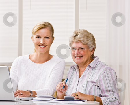 Senior woman writing checks with daughter?s help stock photo, Senior woman writing checks with daughter?s help by Jonathan Ross