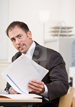 Businessman reviewing paperwork stock photo, Businessman reviewing paperwork by Jonathan Ross