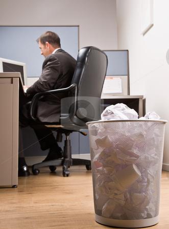 Businessman at desk and trash basket stock photo, Businessman at desk and trash basket by Jonathan Ross