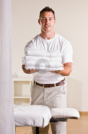 Massage therapist holding stack of towels stock photo, Massage therapist holding stack of towels by Jonathan Ross