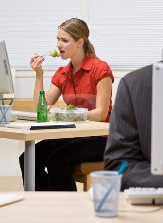 Businesswoman eating salad at desk stock photo, Businesswoman eating salad at desk by Jonathan Ross