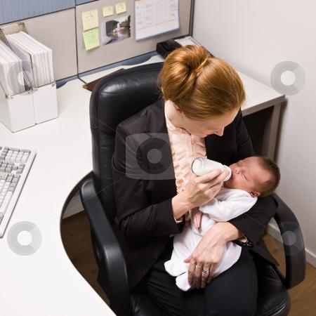 Businesswoman feeding baby at desk stock photo, Businesswoman feeding baby at desk by Jonathan Ross