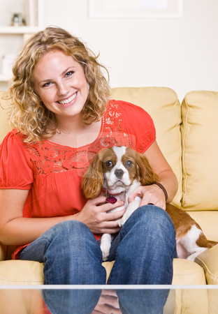 Woman sitting on sofa with dog stock photo, Woman sitting on sofa with dog by Jonathan Ross