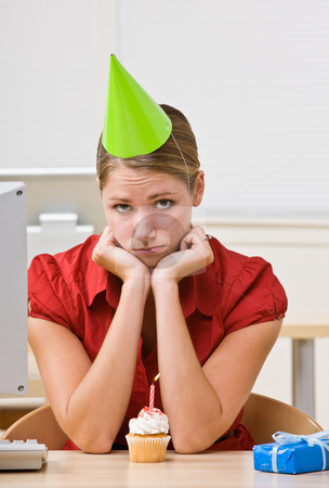 Businesswoman in party hat with birthday cupcake stock photo, Businesswoman in party hat with birthday cupcake by Jonathan Ross