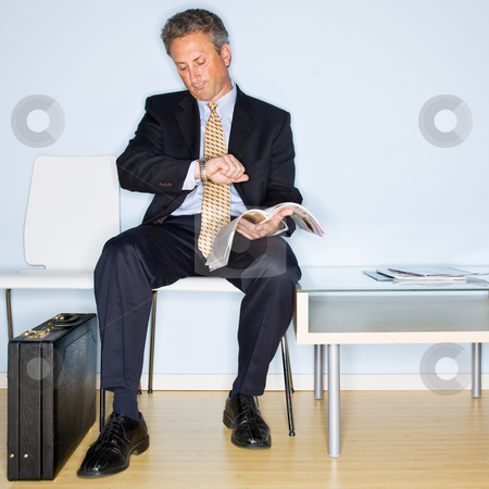 Businessman reading magazine in waiting room stock photo, Businessman reading magazine in waiting room by Jonathan Ross