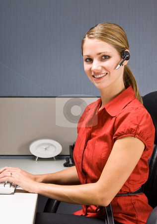 Businesswoman talking on headset at desk stock photo, Businesswoman talking on headset at desk by Jonathan Ross