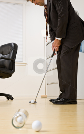 Businessman putting golf ball in office stock photo, Businessman putting golf ball in office by Jonathan Ross