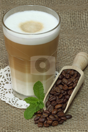 Latte Macchiato stock photo, Latte Macchiato in glass with coffee grain on brown background by Birgit Reitz-Hofmann