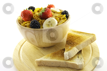 Cornflakes and Toast stock photo, Cornflakes with strawberries, blackberries and banana in a round wooden bowl with a slice of toast on a wooden plate with a white background by Keith Wilson