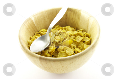 Cornflakes in a Bowl stock photo, Golden cornflakes in a wooden bowl with a spoon on a white background by Keith Wilson