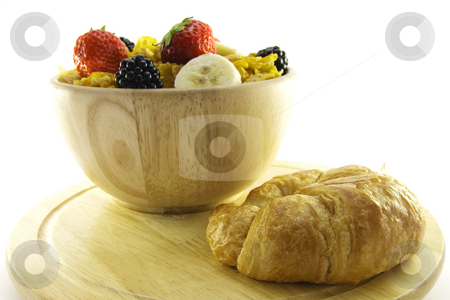 Cornflakes and Croissant stock photo, Cornflakes with strawberries, blackberries and banana in a round wooden bowl with a croissant on a wooden plate with a white background by Keith Wilson