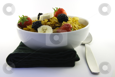 Cornflakes and Fruit with Napkin and Spoon stock photo, Cornflakes with strawberries, blackberries and banana in a round white bowl with a black napkin and spoon on a white background by Keith Wilson